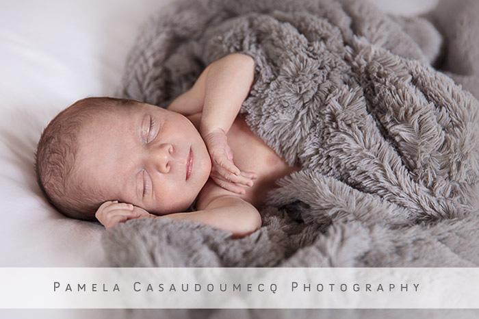 Newborn boy with gray fluffy blanket